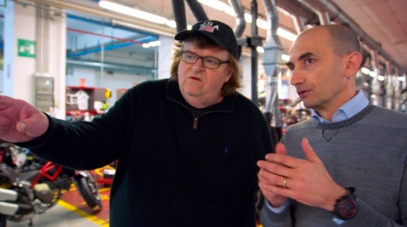 "This image provided by Dog Eat Dog Films shows director Michael Moore, left, and Claudio Domenicali, CEO of Ducati, in a scene from his documentary, ""Where to Invade Next."" The movie opens in U.S. theaters on Feb. 12, 2016. (Dog Eat Dog Films via AP)"